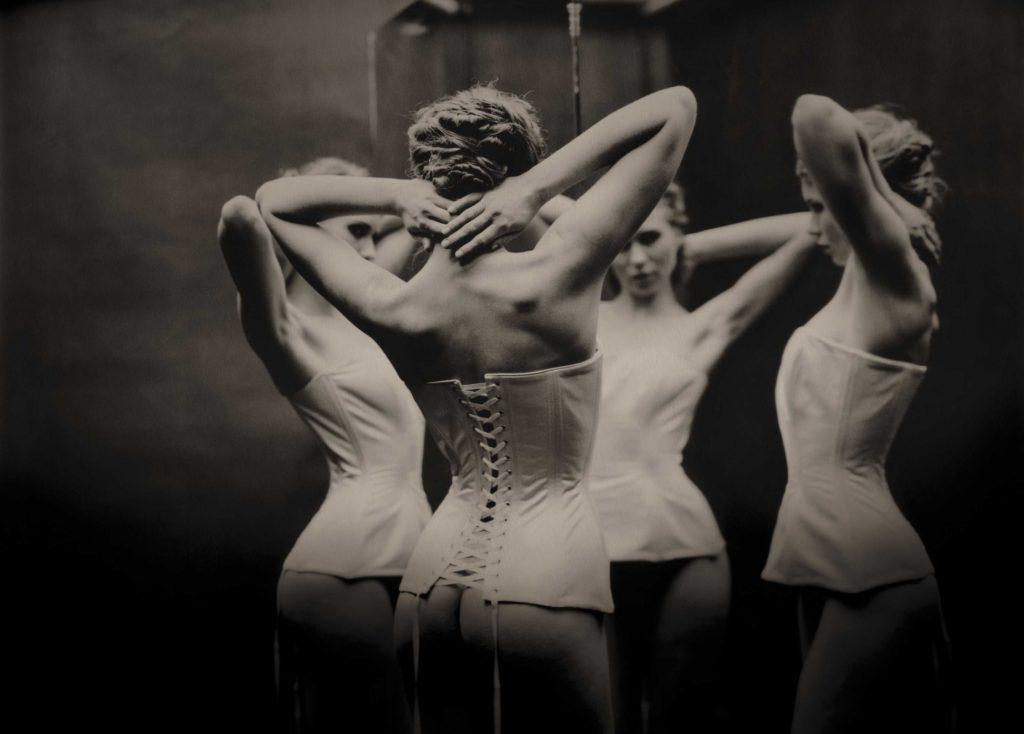 vrouw in corset voor 3 spiegels